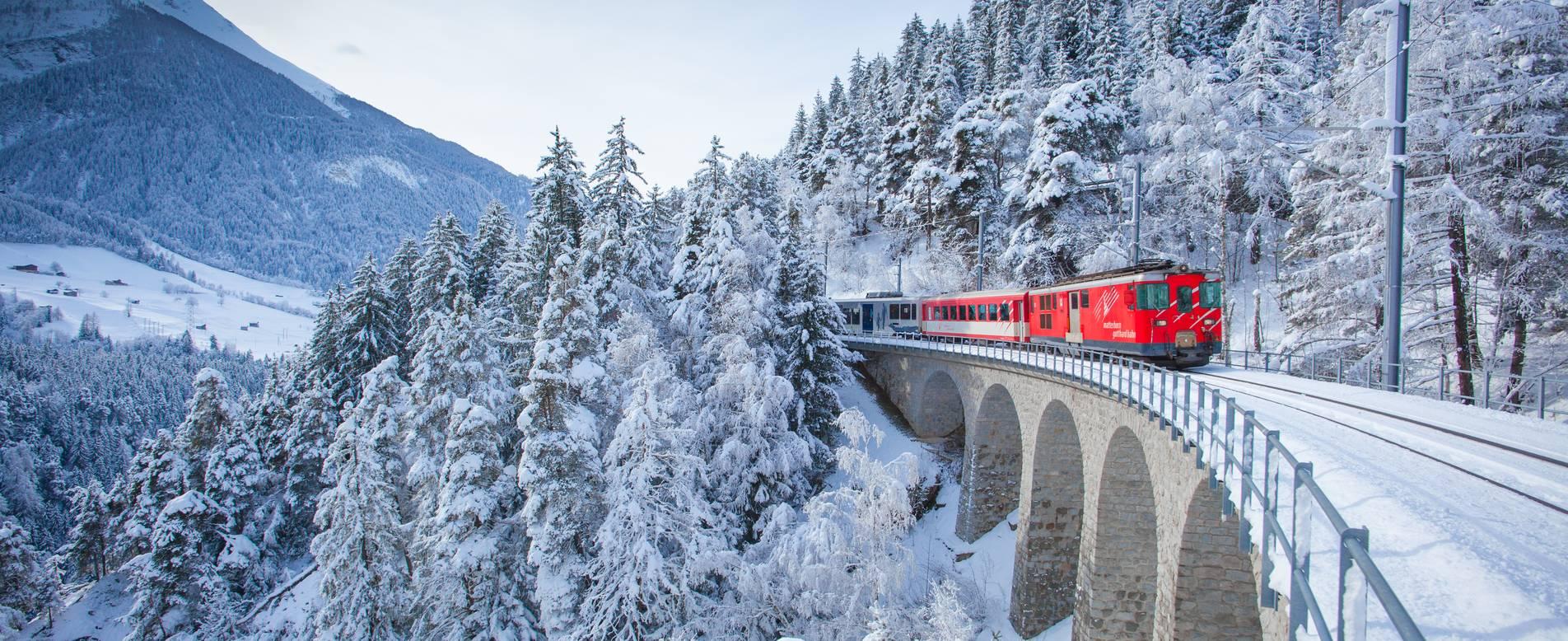 Đoàn tàu hỏa màu đỏ đi xuyên qua vùng rừng đông tuyết phủ