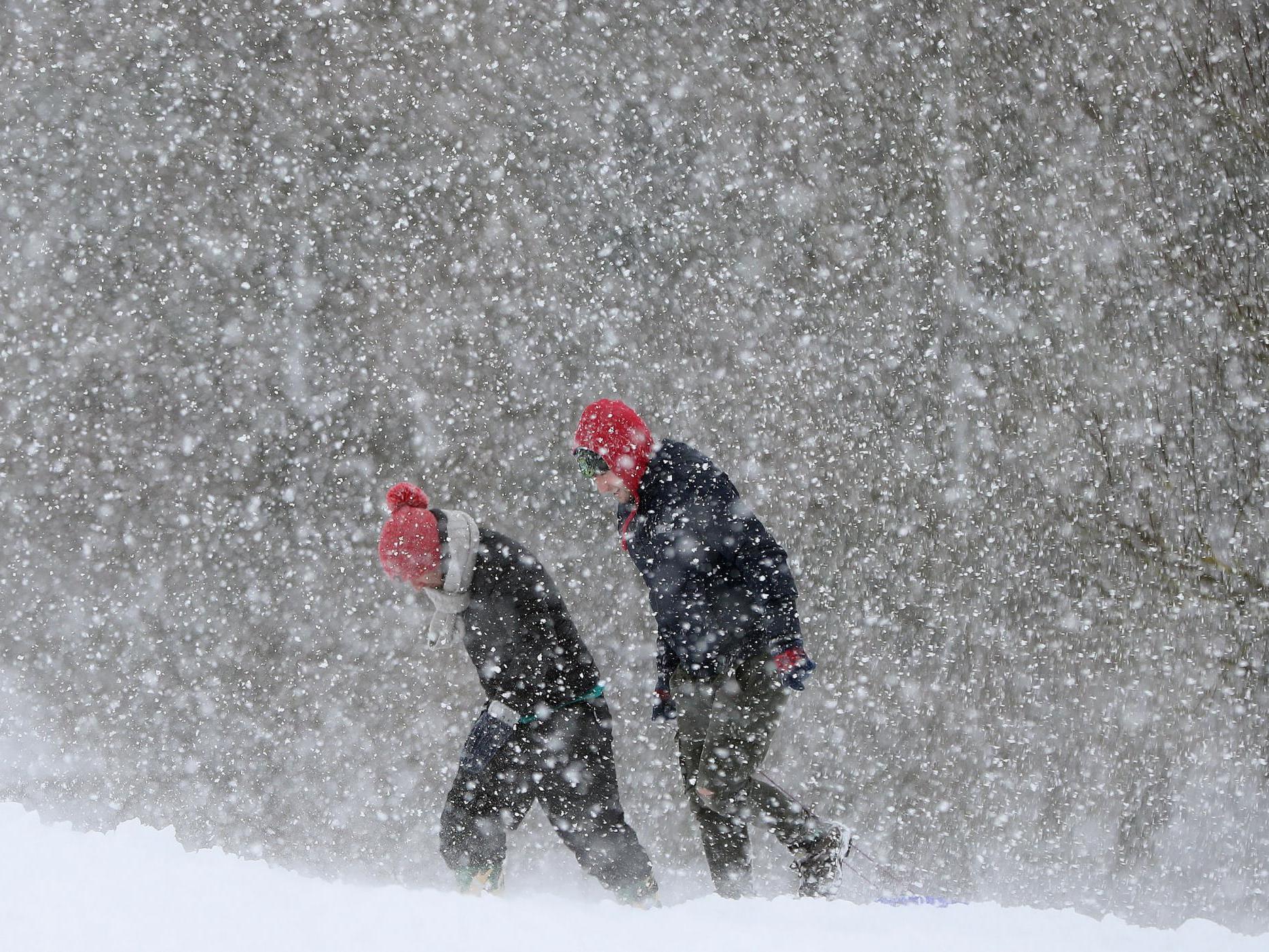 Hai người đi bộ trong trời tuyết trắng xóa mùa đông