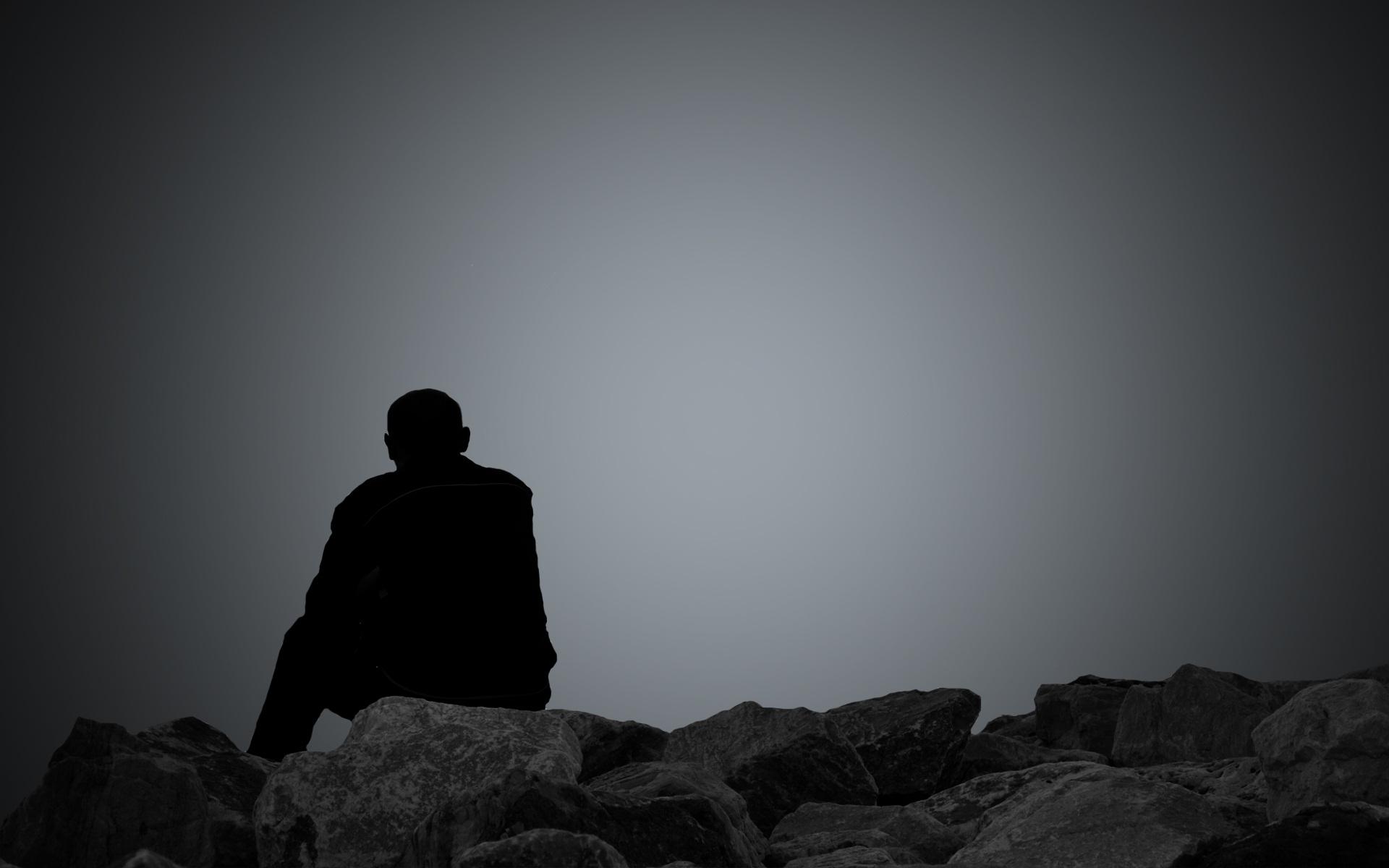 Hình nền người ngồi ở bãi đá cô đơn