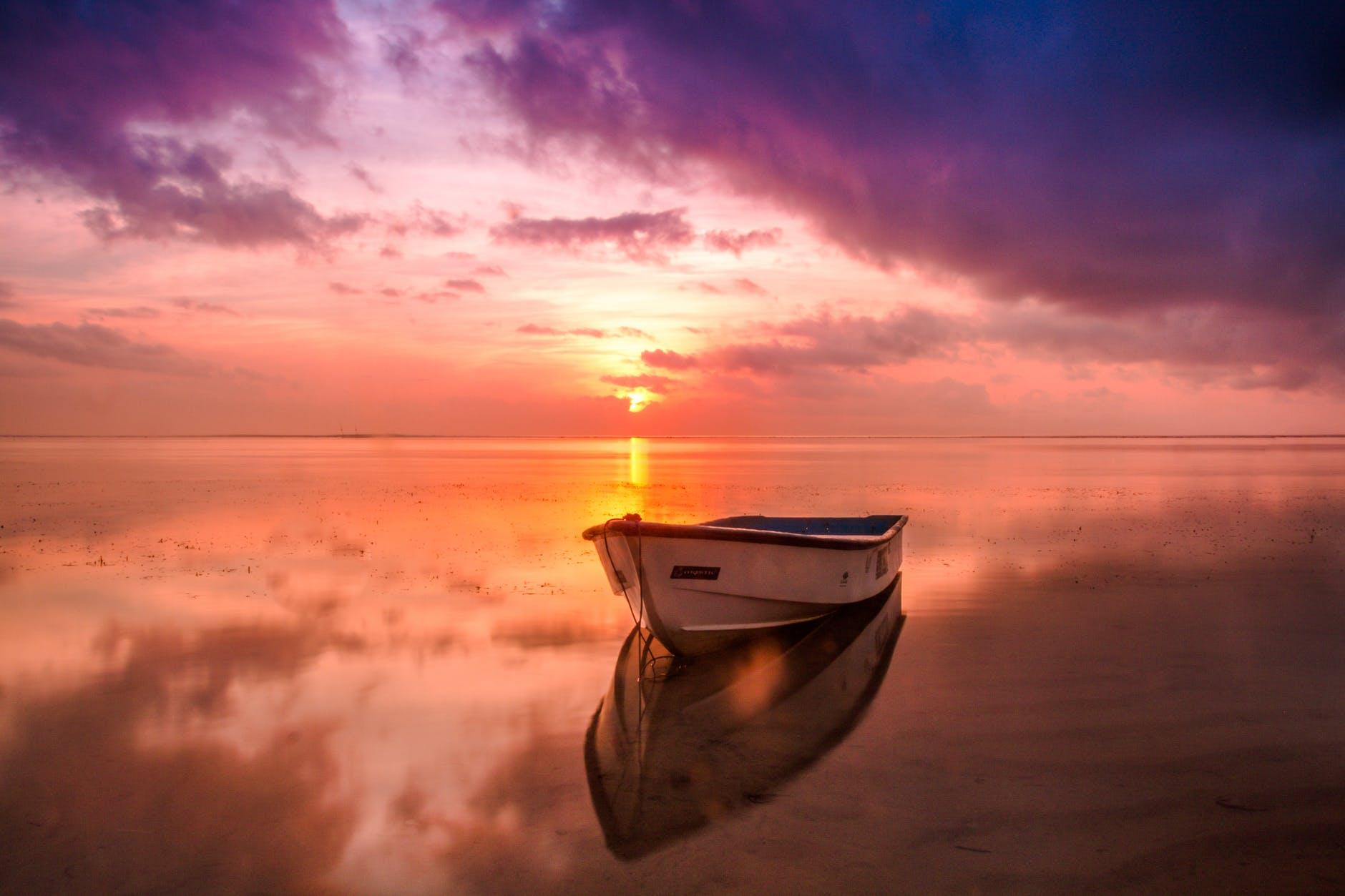 Hình ảnh bình minh trên biển và con thuyền đơn sơ