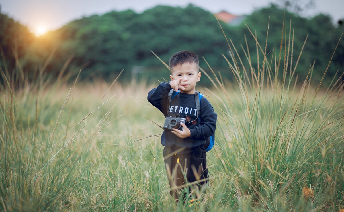 Hình ảnh bé trai đứng trên đồng cỏ