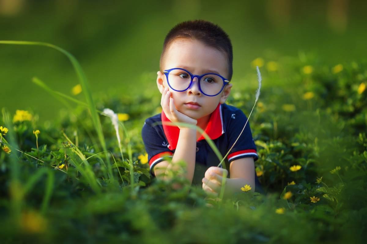 Hình ảnh cậu bé trai chống má đeo kính