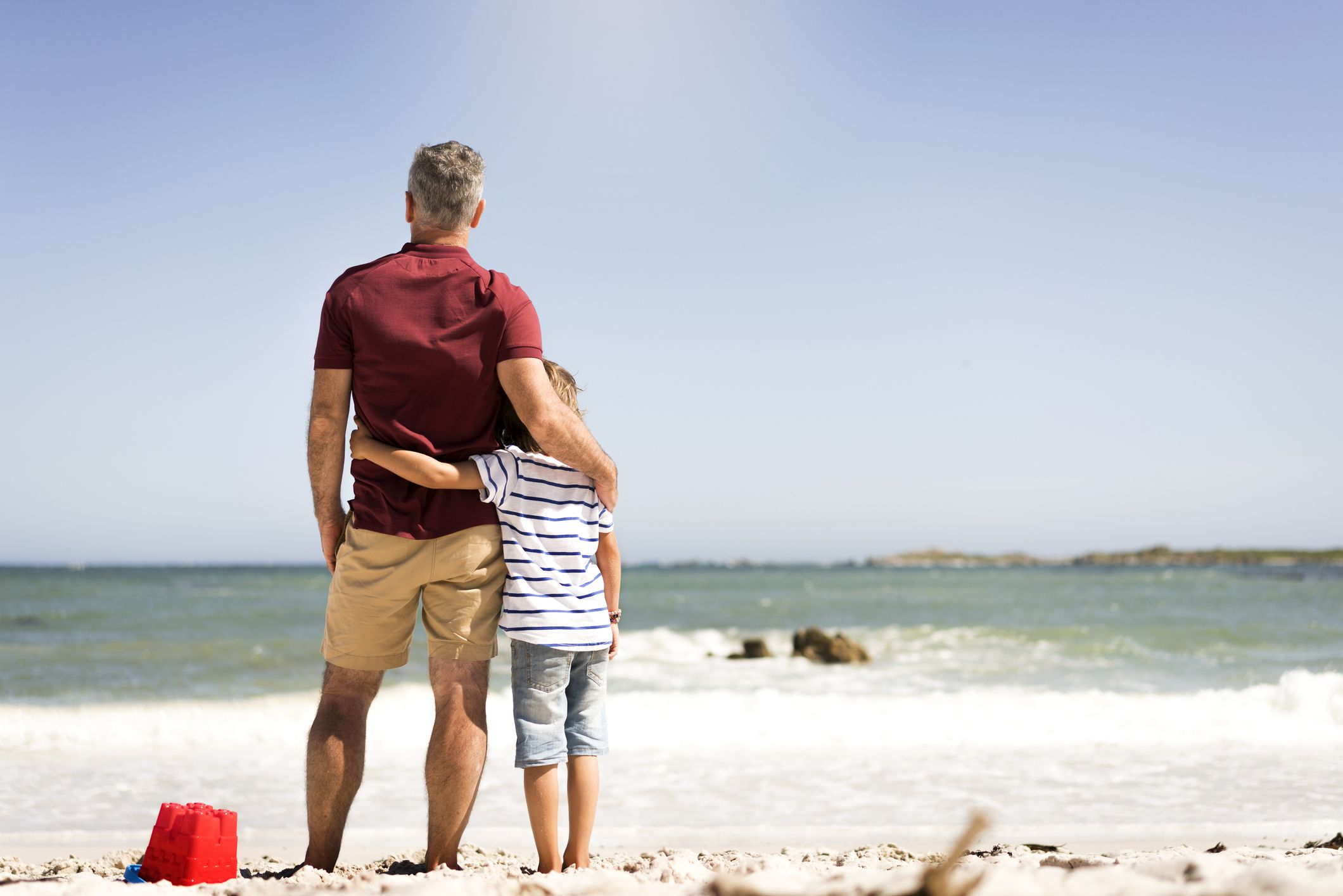Hình ảnh cha và con cùng nhau đứng trên bờ biển cát trắng