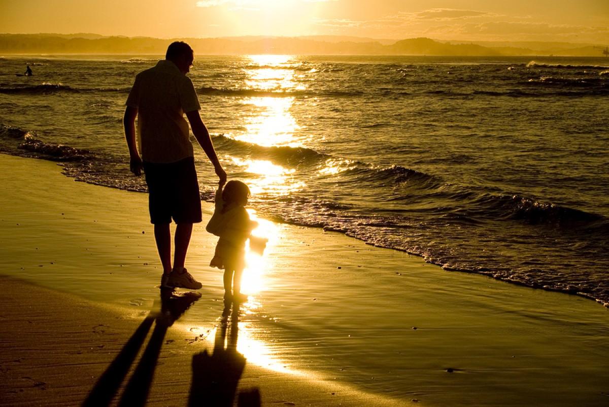 Hình ảnh cha và con gái dắt tay nhau đi trên bờ biển