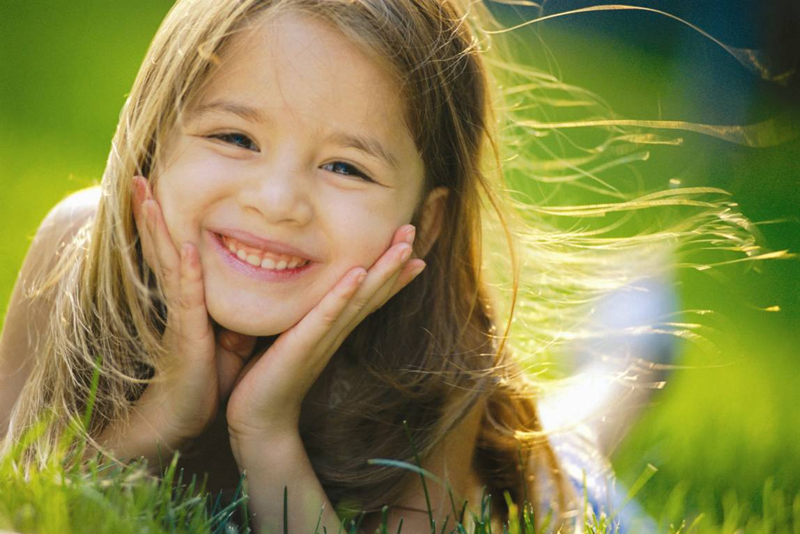 Hình ảnh trẻ em bé gái nằm trên đồng cỏ