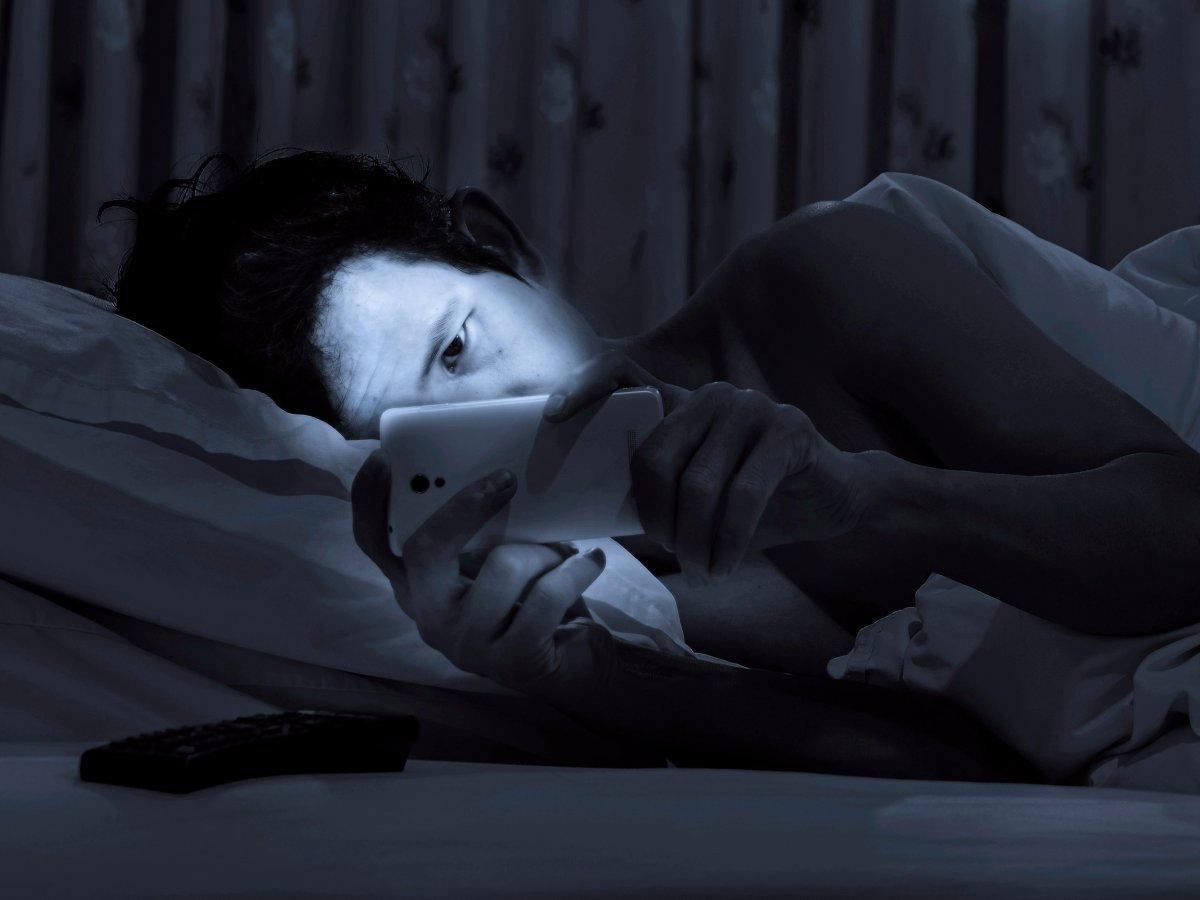 Hình ảnh người khó ngủ xem điện thoại