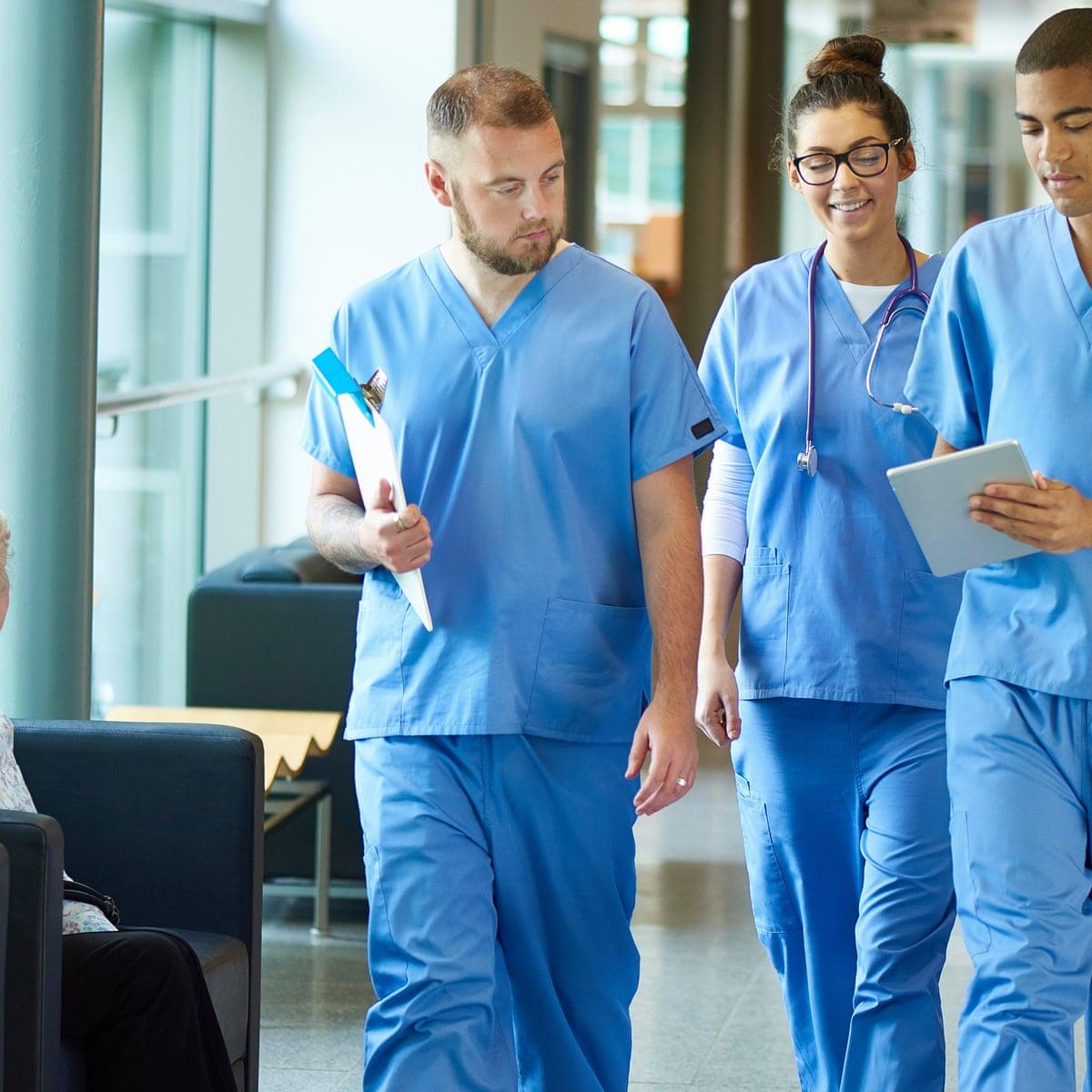 Hình ảnh ba bác sĩ trong trang phục áo xanh đang bàn công việc