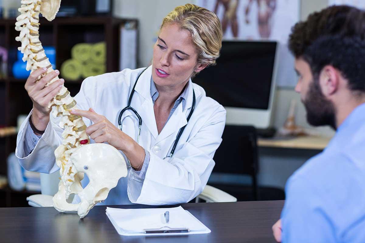 Hình ảnh bác sĩ cầm xương đốt sống chỉ cho bệnh nhân